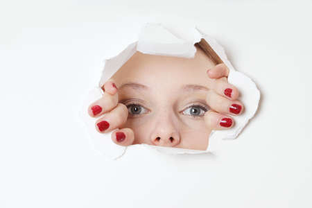 young woman peeking through hole in paper wall photo