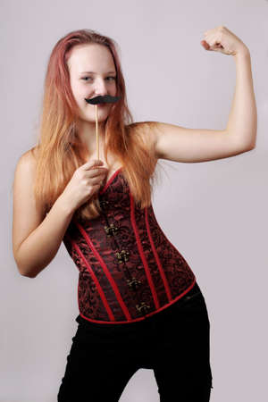 transgender: young woman with fake moustache on a stick showing off biceps muscle Stock Photo