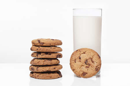 bickie: chocolate chip cookies and glass of milk on white Stock Photo