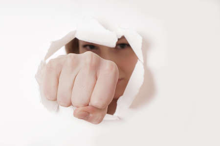 white hole: woman punching hole through paper wall with fist