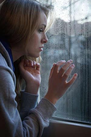 triest jonge vrouw kijkt door raam met regendruppels