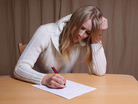 lovelorn: lovesick young woman writing letter with broken heart Stock Photo