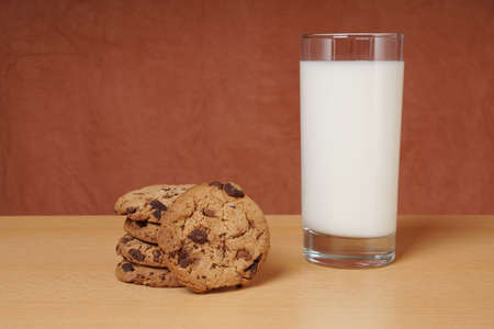 bickie: chocolate chip cookies and glass of milk on table Stock Photo