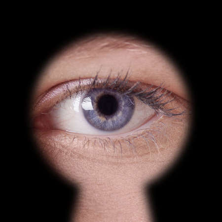close-up of human female blue eye looking through keyhole Stock Photo