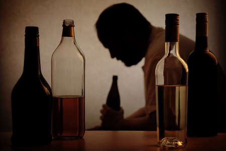 depressed man: silhouette of a person drinking behind bottles of alcohol with added filter