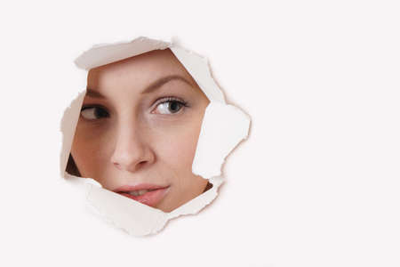 furtively: young woman peeking through hole in paper wall Stock Photo