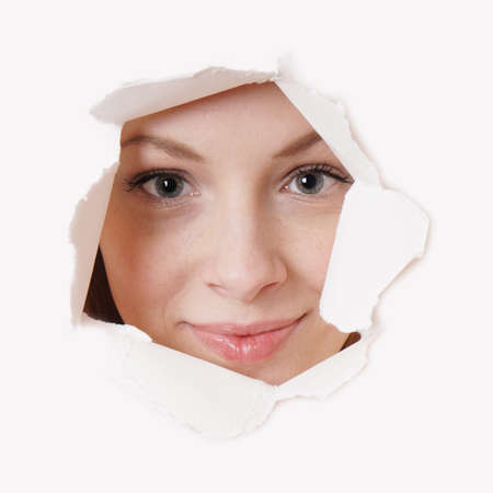 voyeur: smiling young woman peeking through hole in paper wall Stock Photo