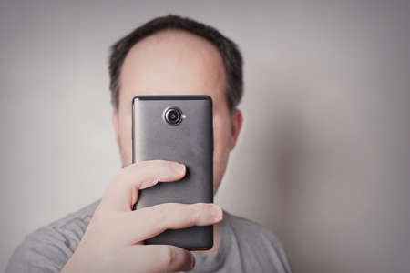 funny guys: man looking at smart phone or taking selfie picture with camear mobile