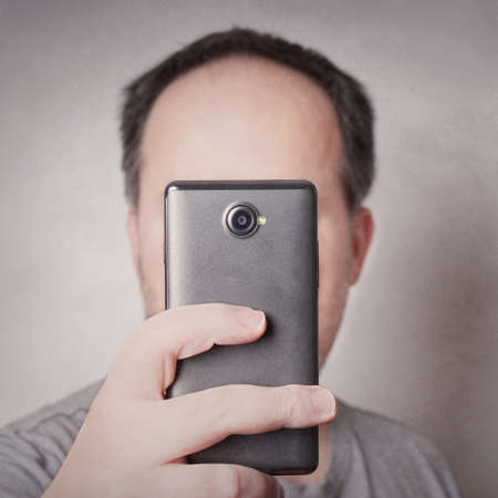 man taking selfie picture with smart phone camera looking like a cyclops with added filter