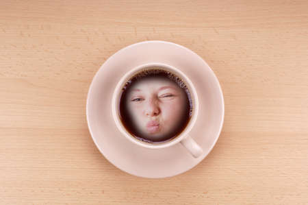 puckered lips: cup of black coffee with female face with puckered lips kiss