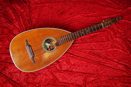 vintage lute string instrument on red velvet background Stock Photo