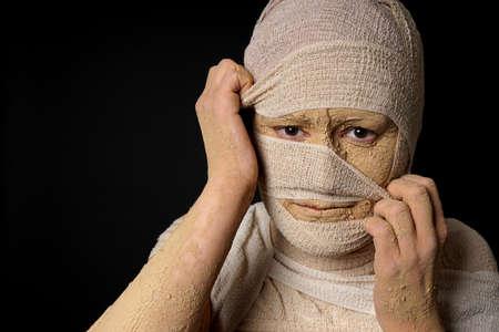 mummification: female egyptian mummy pulling at bandages halloween concept