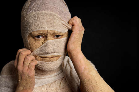 mummification: grungy female egyptian mummy pulling at bandages halloween concept Stock Photo
