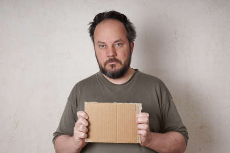 grouchy: grubby scruffy man holding blank cardboard sign Stock Photo