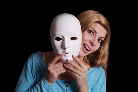若い女性が彼女の顔から普通の白いマスクを削除します。 写真素材