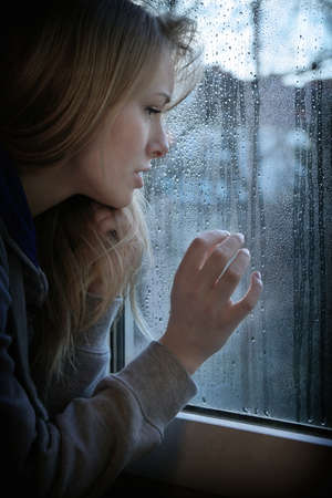 melancholic young woman looking through window with raindrops with added filter grain and vignette