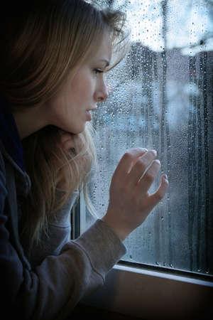mujer joven melancólica mirando por la ventana con las gotas de agua con filtro de grano añadido y viñeta Foto de archivo