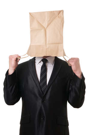 humiliated: business man pulling brown paper bag over his head to hide his face
