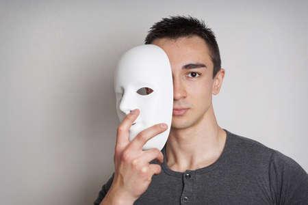 hombre joven que saca la cara reveladora máscara blanca llana Foto de archivo