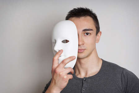 young man taking off plain white mask revealing face Stock Photo