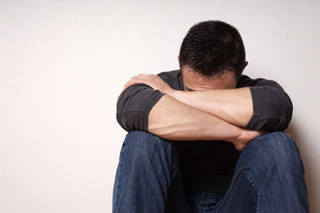 men face: depressed brokenhearted young man hiding his face