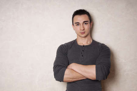 ambiguous: young man with arms folded or crossed leaning against wall