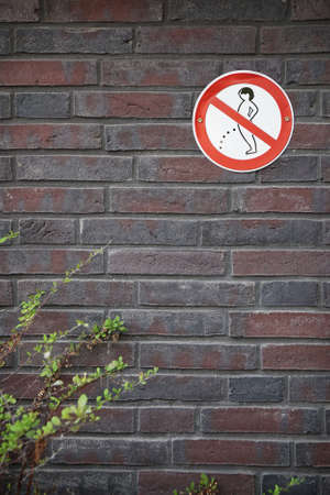 prohibition sign forbidding peeing in public on wall Stock Photo