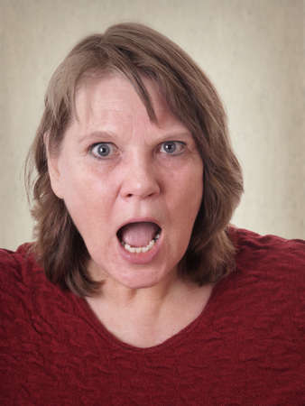 outcry: mature senior woman shocked with open mouth Stock Photo