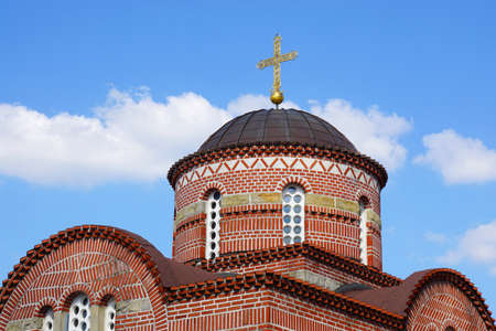 religious building: serbian orthodox church building with dome and cross