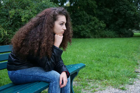 teen: sad female teenager sitting on park bench