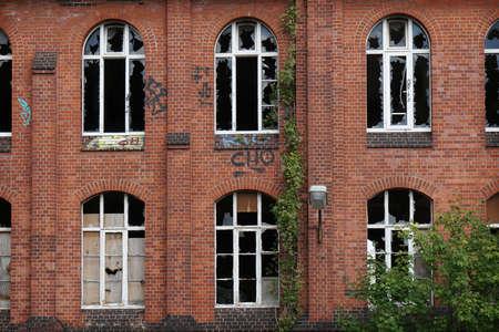 Fachada: abandonada fachada de ladrillo rojo con ventanas rotas