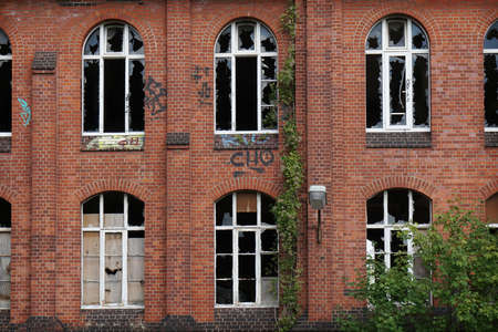 building wall: derelict red brick facade with broken windows