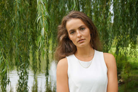 weeping willow: young woman wearing a white dress standing in front of a weeping willow tree in a park