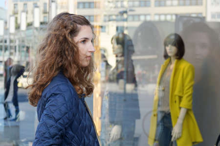 tienda de ropa: Mujer joven que mira la pantalla de la moda en el escaparate