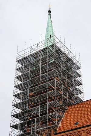renovate old building facade: church tower or steeple or spire with scaffolding