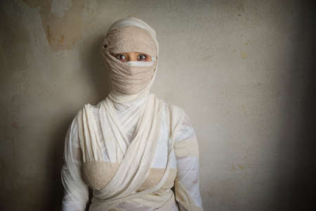 mummification: woman wrapped in bandages as egyptian mummy halloween costume