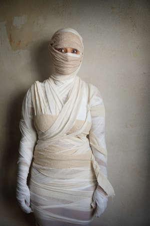 エジプトのミイラのハロウィーンの衣装と包帯に包まれた女性