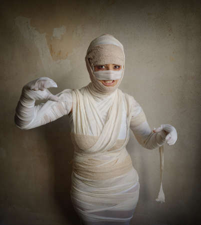 mummification: woman wrapped in bandages as egyptian mummy halloween costume fletching teeth Stock Photo