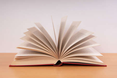 open hardcover book with turning pages in fan shape on desk Banque d'images