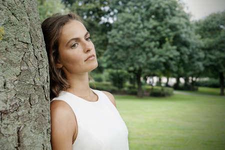 mirada triste: Mujer joven triste que se inclina contra árbol con efecto retro filtro