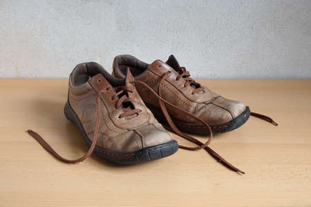 scuffed: pair of shabby old battered mens leather shoes Stock Photo