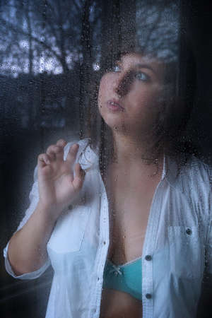 melacholic young woman looking through window with raindrops Stock Photo