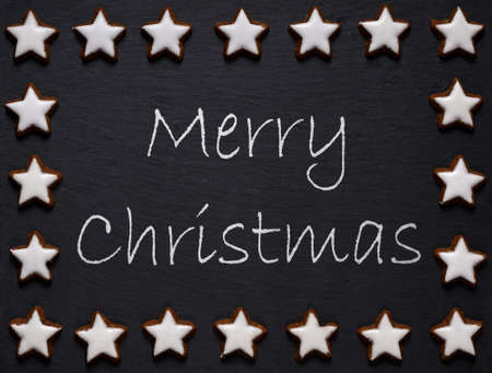 bickie: merry christmas written on slate with star shaped cookie decoration