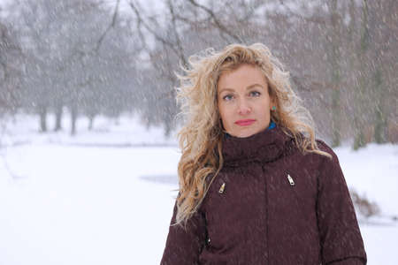 snowstorm: blond woman standing in heavy snowfall or snowstorm
