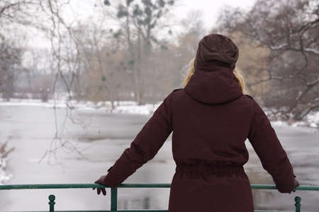 gazing: rear view of lonely woman standing on bridge gazing over frozen river in winter