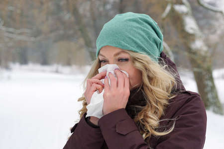 blow: woman suffering from cold blowing her nose with tissue outdoors in winter