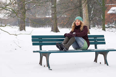 girl sit: lonely woman sitting on snow covered park bench in winter Stock Photo