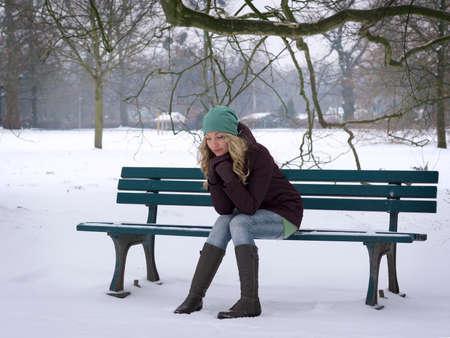 soledad: Mujer sentada sola en la nieve cubre Banco del parque con la depresión de invierno