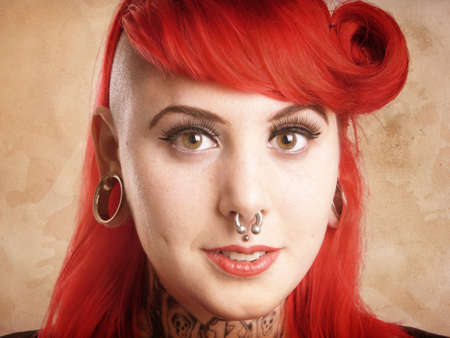 pierced ears: young alternative woman with side cut, facial piercings and tattoos - with added texture filter effect
