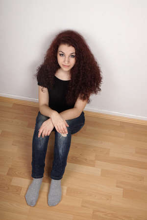 long socks: young woman sitting on laminate floor in empty room